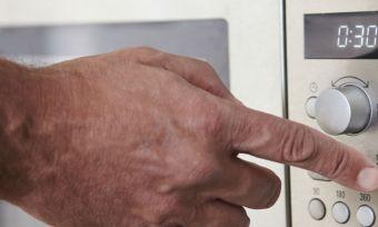 Man touching microwave