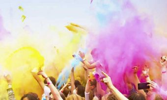 People dancing with coloured powder