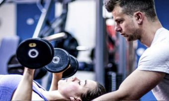 Client and trainer lifting weights at the gym