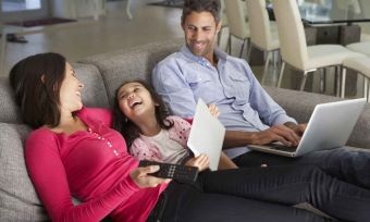 Happy family on sofa with laptop and tablet