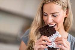 Woman biting a chocolate bar