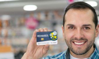 Man holding up loyalty program card