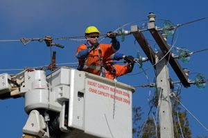 A linesman wires up a mains power supply