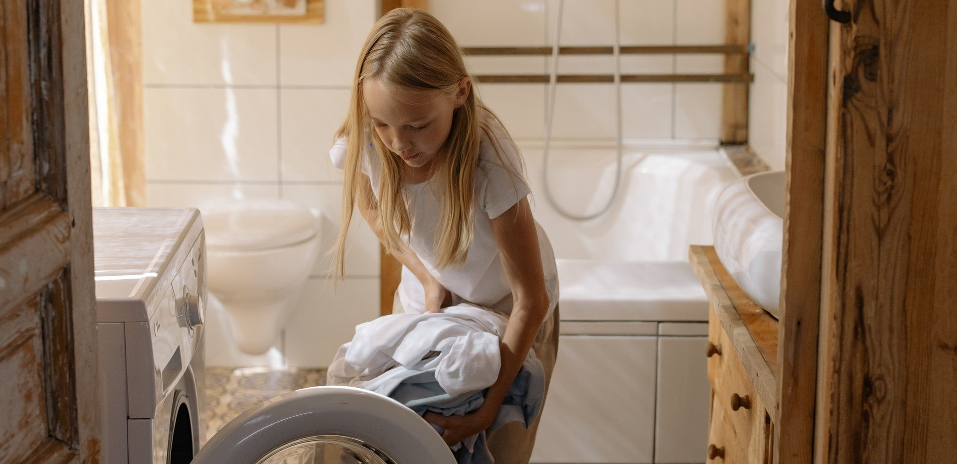 girl putting clothes into dryer